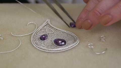 Master jeweler with professional tweezers putting the gem on the necklace