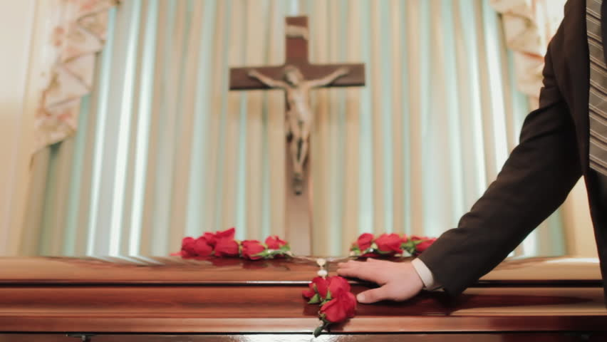 Person visiting coffin at christian funeral service