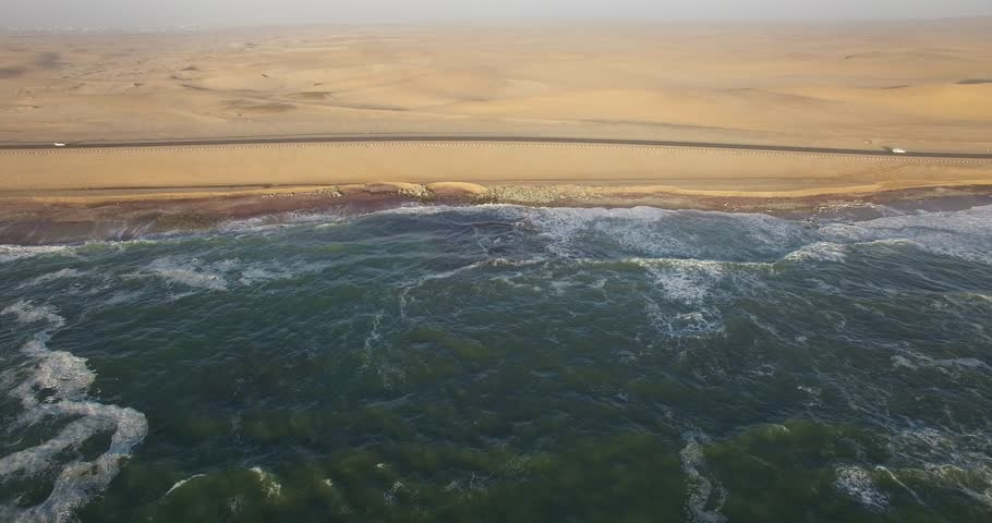Aerial drone view of Namibian Atlantic coastline, road along the coast from Swakopmund to Walvis Bay,  beach, surf break point, landscape with ocean background of sand dunes at Namibia's west coast