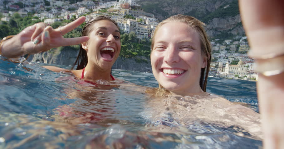 Girl friends taking selfie photograph in water with Positano town in background Tourist women enjoying European summer holiday travel vacation adventure in Amalfi Coast Italy