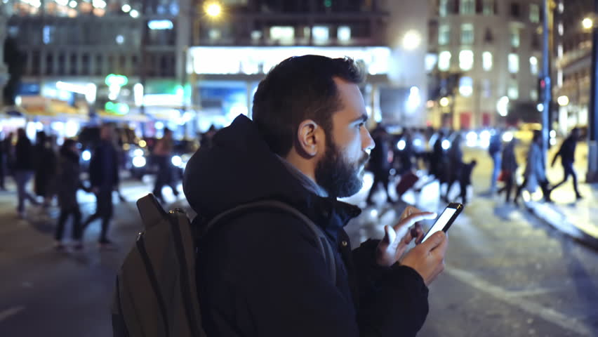 A young man is commuting to work while browsing his cellphone on a busy urban street at night. #24940412