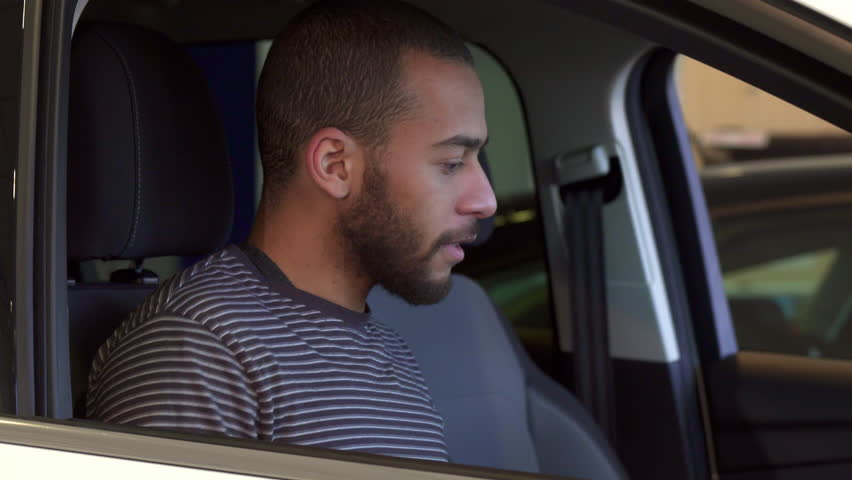 Young african american man sitting down into the car at the dealership. Attractive bearded guy closing the door. Handsome brunette male customer showing his thumb up inside the car | Shutterstock HD Video #24941732