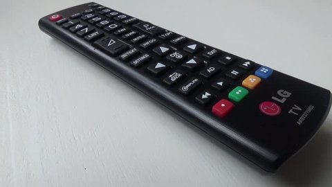 Overview of the buttons of a black lg tv remote located on a white table,  march 12, 2017