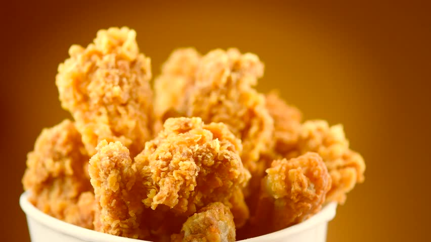Rotation Bucket full of crispy fried chicken on brown background. UHD video footage. Ultra high definition 3840X2160 4K