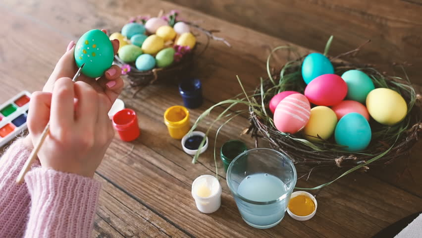 Female hands painting Easter eggs on dark wooden table. Selective focus. | Shutterstock HD Video #24969902
