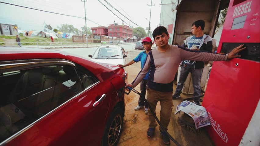 KATHMANDU, NEPAL - MAY 14, 2016: Driver refuels his car at petrol station. Others wait in the queue