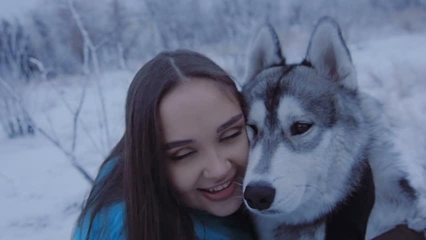 Beautiful girl hugging a husky dog.