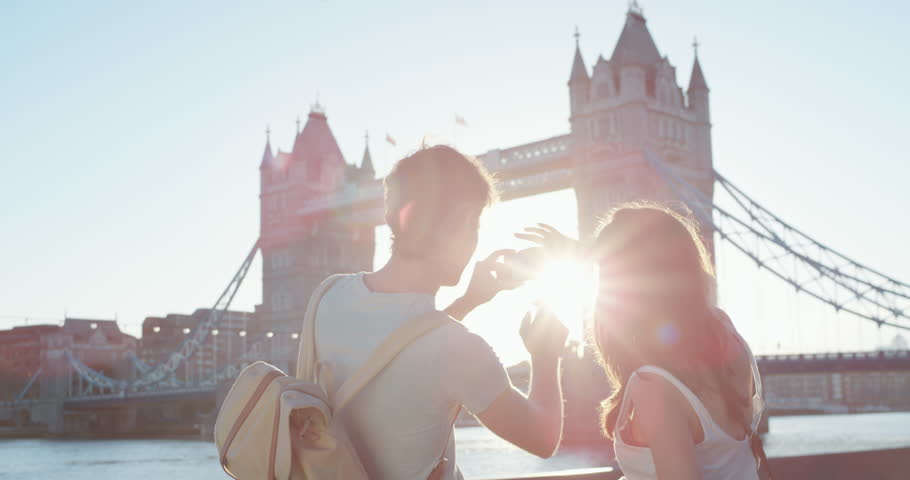 Tourist couple taking photograph of tower bridge London using smartphone photographing scenic cityscape view enjoying vacation travel adventure