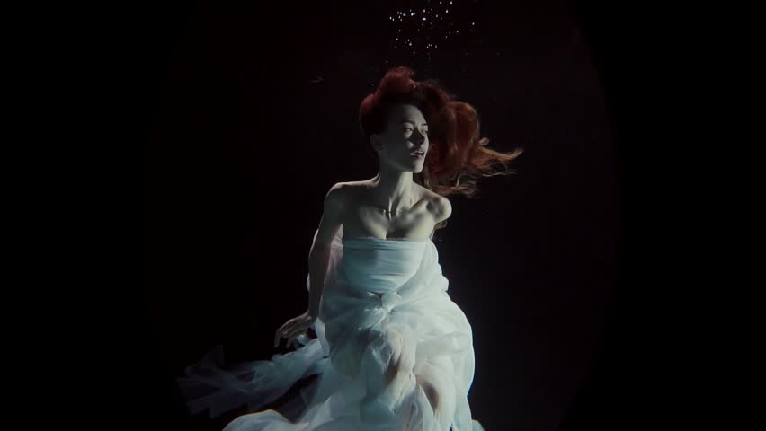 Young woman swimming under the water on a black background | Shutterstock HD Video #25053284