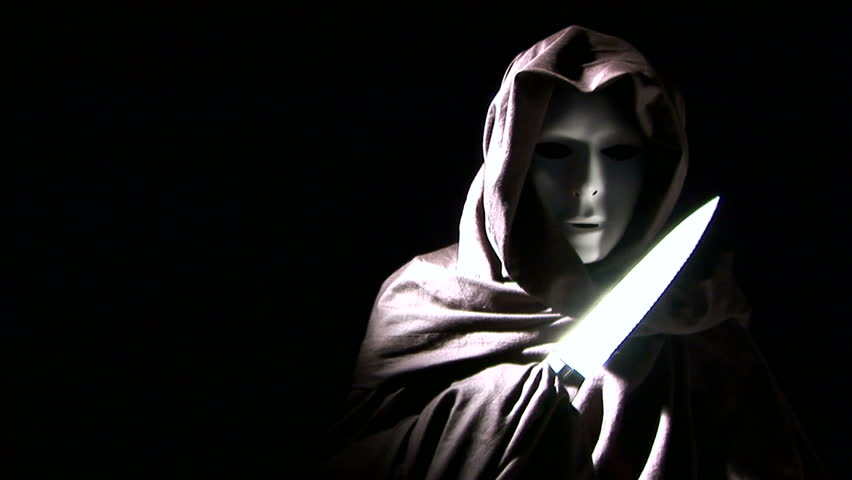 A person masked and cloaked in black, flashing a knife.