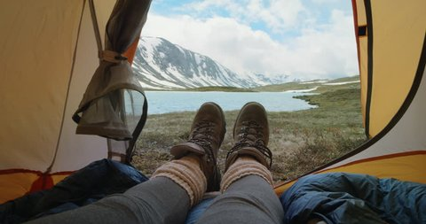 Camping woman lying in tent Close up of Girl feet wearing hiking boots relaxing on vacation POV