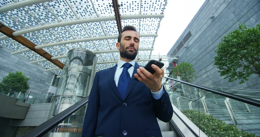 On escalators, a businessman answers the phone, send messages and smiles for the beautiful job news. Concept: technology, telephony, business trips, business.