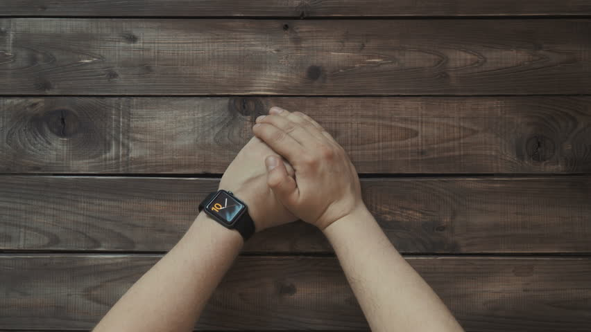 Making various gestures with a finger on a touch screen of a smart watch wearable device. Wooden background