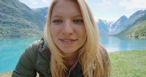 Beautiful woman filming dancing video using smartphone outdoors glacial lake Crazy Vlogger Girl Sharing selfie dancer video on social media travel vlog enjoying Norway vacation travel adventure