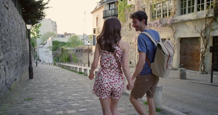 Romantic tourist couple holding hands walking streets of Paris wearing cute summer dress hand in hand enjoying European summer holiday travel vacation adventure | Shutterstock HD Video #25098512