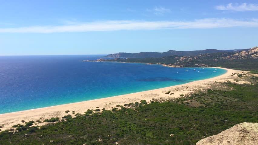 Long sandy beach in a rocky landscape from a bird's eye view