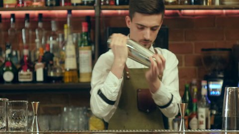Barman shaking cocktail and pouring it to an empty glass at a nightclub