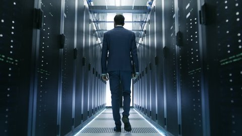 Following Shot of IT Engineer Walking Through Data Center with Rows of Working Rack Servers on Both Sides. Shot on RED EPIC-W 8K Helium Cinema Camera.