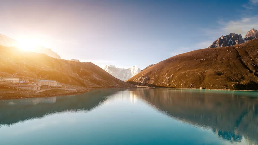 Beautiful snow-capped mountains at sunrise with Gokyo lake against the blue sky. Exploring beauty world: trekking in Himalaya, Nepal. Travel background. Slow motion 4K footage