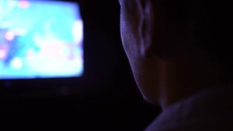 Young Man Absorbed In Online Video Game at night. Man watching TV