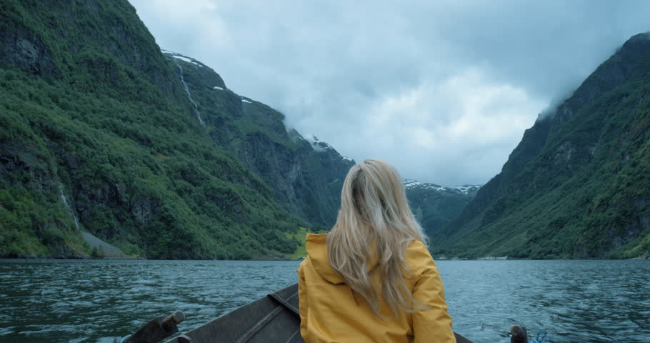 Brave Woman taking photograph in stormy weather on Fjord Norway with smartphone photographing scenic landscape nature background view enjoying vacation travel adventure #25126922