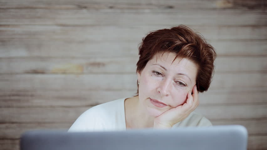 Sleepy bored woman sitting at office desktop with laptop, working and yawning in office