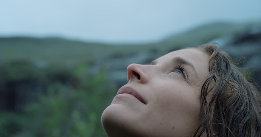 Close up portrait of Woman looking up at rain in nature with wet hair Hiker Girl trekking in Scotland Slow Motion