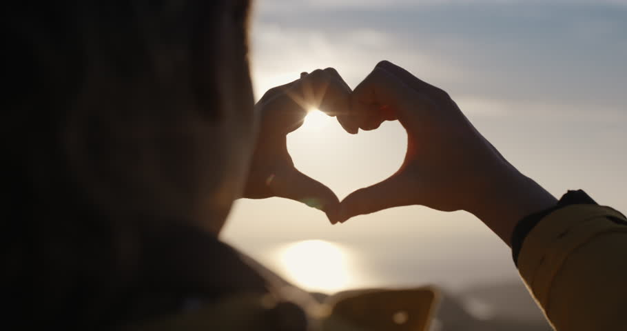 Beautiful Woman making heart shape with hands at sunset Girl holding up love symbol gesture with orange sun flare | Shutterstock HD Video #25169432