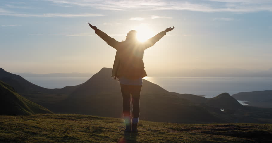 Woman with arms raised on top of mountain looking at Sunrise view Hiker Girl lifting arm up celebrating scenic nature landscape enjoying vacation travel adventure Isle of Skye Scotland | Shutterstock HD Video #25169552