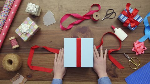 Aerial footage of woman tying red ribbon on gift. Lockdown shot of female packing present at wooden table. Overhead flat lay of art and craft equipment surrounding lady's hands.