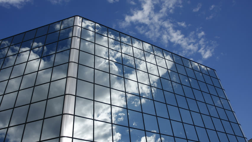 building an office.  office active clouds are reflected in the mirrored windows of an office building  hd timelapse  intended building an office