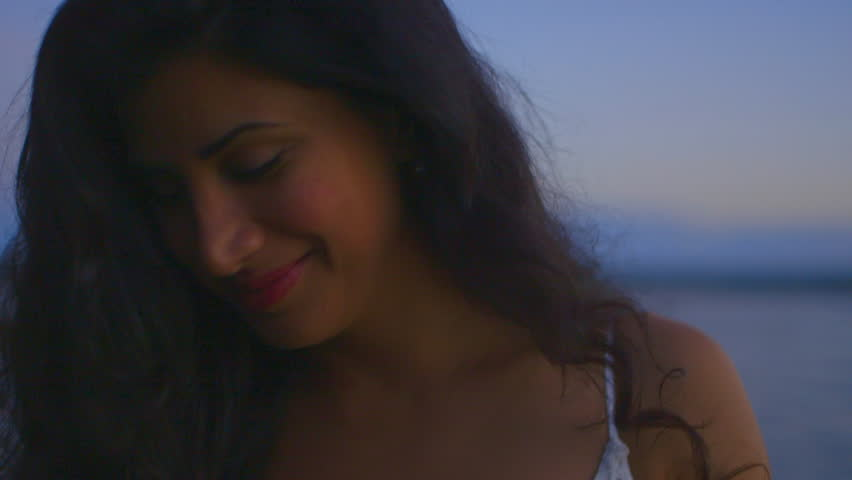 Slow motion close up shot of a woman at the beach looking at the camera and smiling shyly. Continues. #25197122