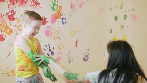Young mother with her little boy are lmixing colors at their hands yo leave beautiful handprints on the wall. Their clothes are dirty in color. Mother and child concept. Slowmotion.
