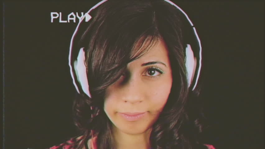 Fake VHS tape: a beautiful young woman listening to music with headphones, feeling uncomfortable, smiling to hide her hindrance. Close-up shot on black background.