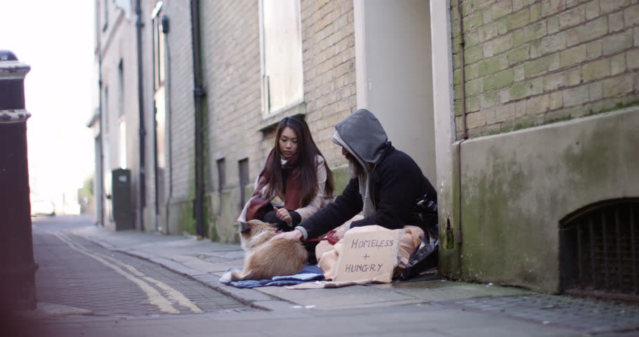 4k, A young woman talking to a homeless person and petting his loyal pet dog. Slow motion.