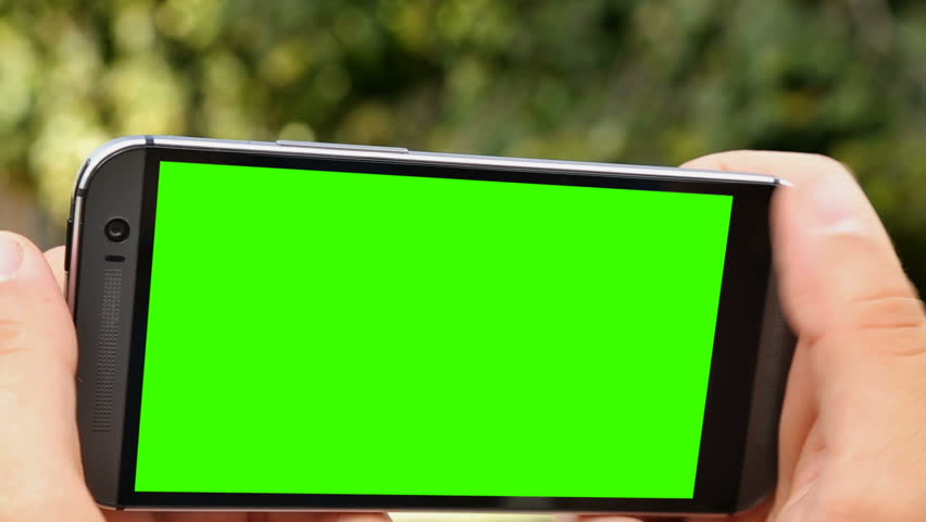 Person making 360 degree video on smartphone with green screen, alpha channel.