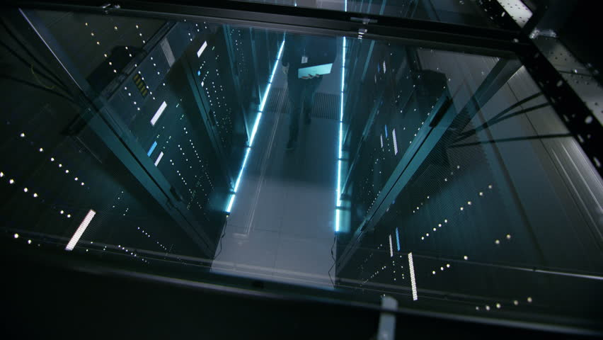 Top View Through the Glass of IT Engineer Working with Laptop in Data Center Full of Active Rack Servers. Shot on RED EPIC-W 8K Helium Cinema Camera. | Shutterstock HD Video #25242302