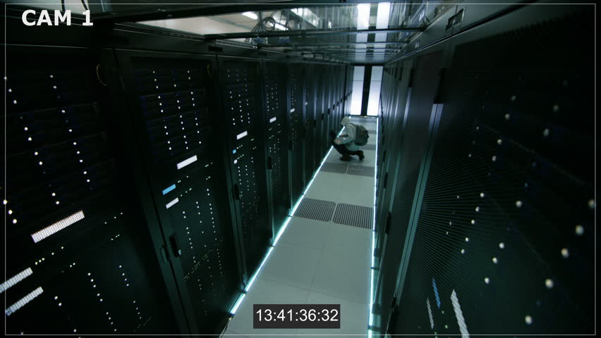 Security Camera N1 Footage of a Hooded Hacker in Data Center, With His Laptop He Connects to One of The Rack Servers, Commits Crime and Leaves. Shot on RED EPIC-W 8K Helium Cinema Camera.