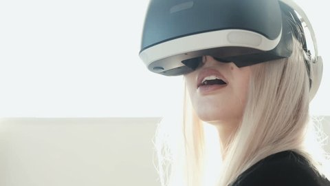 Future is now. Beautiful young female playing game in vr glasses. Beautiful woman touch something using modern virtual reality glasses