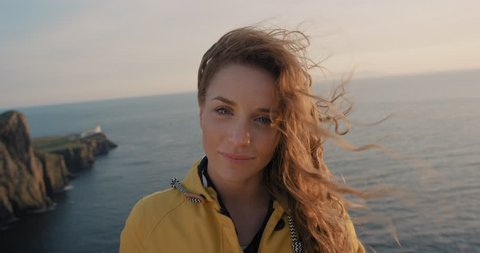 Independent Woman smiling with Red hair blowing in wind Close up portrait looking at sunset over ocean Young Girl wearing yellow raincoat trekking in Scotland Slow Motion