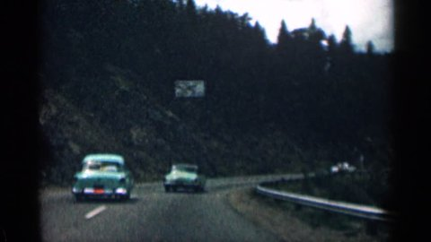 MINNESOTA 1963: people are driving cars on a secluded road where there's lots of trees