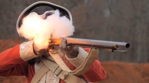 VIRGINIA - OCTOBER 2016 - American Revolution era British Redcoat Soldier. Re-enactors, reenactment.  Firing Brown Bess musket gun with black powder and lead bullets in earthen fort in battle.