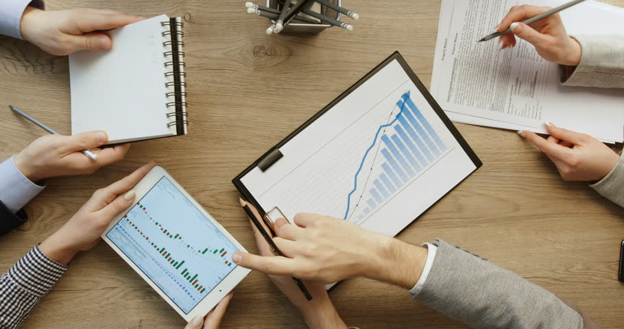 Hands top view. Business. Team working together at office desk, man is working with tablet and checking financial reports and woman are writing, noting information in notebook. Slow motion. red epic | Shutterstock HD Video #25279499