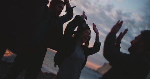 Cool young hipster friends doing high five and having fun on a beach at sunset