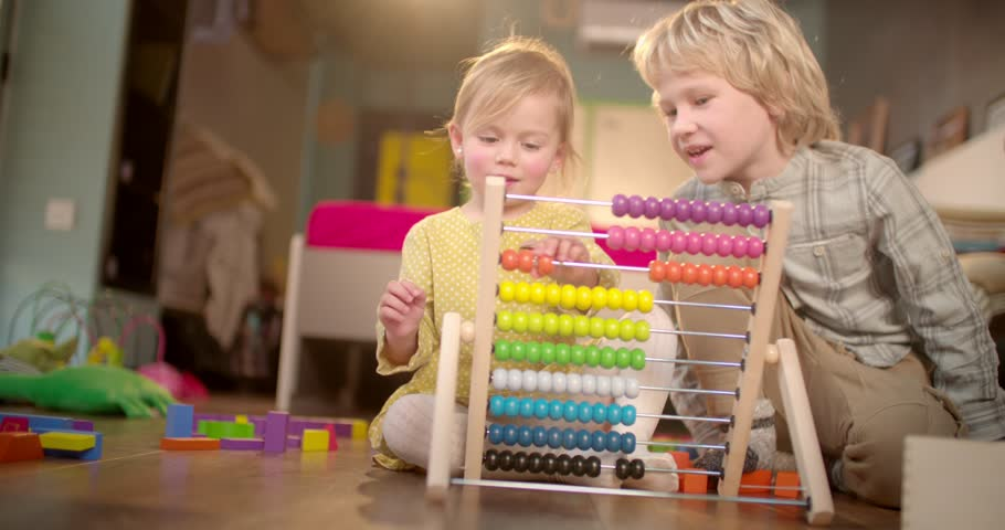 Little sister learning how to count on abacus with the help of her older brother