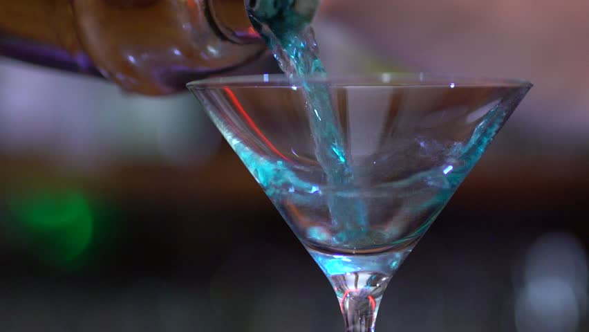 SLOW MOTION: Close up shot of a blue cocktail being poured into a martini cocktail glass in a bar.