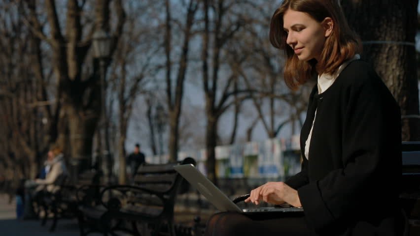 A young girl in the park sitting on a bench typing and looking at the sun smiled. She is happy with this day and happy  | Shutterstock HD Video #25304702