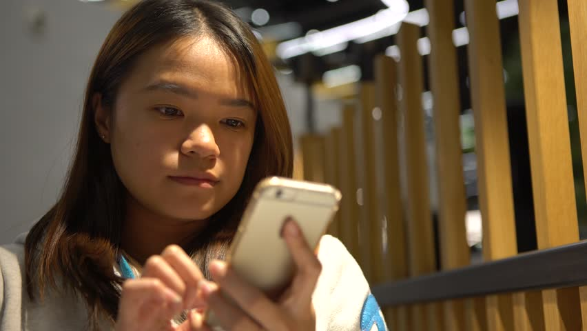 4K Beautiful Asian Woman Waiting on the Restaurant is a good time to get some work done on your phone device, using smartphone for cheks her e-mail and writting text, as she waits. | Shutterstock HD Video #25309982