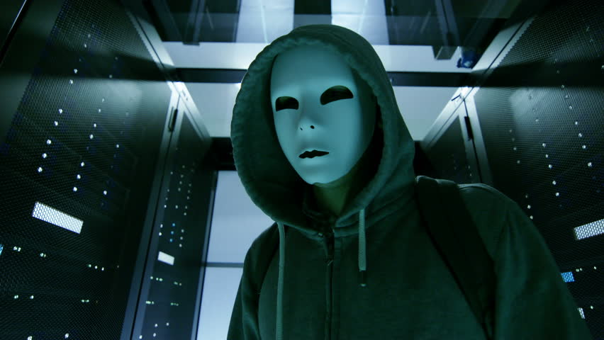 Masked Hacker in a Hoodie Walks Through Corporate Data Center with Rows of Working Rack Servers. Shot on RED EPIC-W 8K Helium Cinema Camera.