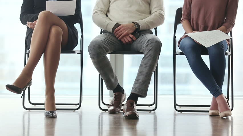 Ready to get new career. Group of three young businesspeople sitting on chairs in office, waiting and going for job interview, feeling nervous. Body language. Close up of legs. Job search concept